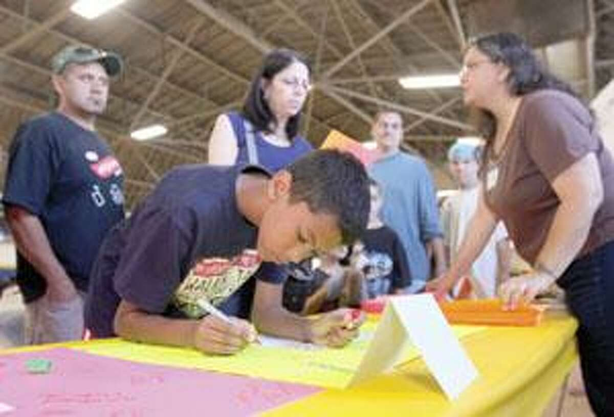 SONJA ZINKE/Register CitizenDelvin Alvarez, 10 of Torrington signs a large Thank You card as he passes through the line at the second annual Jr. Dress for Success event held by the Torrington Early Childhood Collaborative Saturday at the Armory in Torrington. Purchase a glossy print of this photo and more at www.registercitizen.com