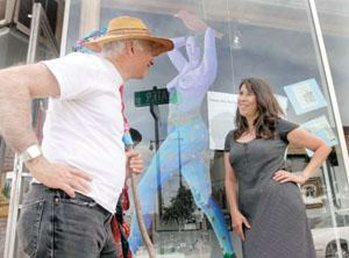 SONJA ZINKE/Register CitizenArtist Danielle Mailer talks with Artwell Executive Director, Stewart Wilson on the sidewalk on Water Street in Torrington with one of her works of art behind the window Saturday afternoon. Purchase a glossy print of this photo and more at www.registercitizen.com