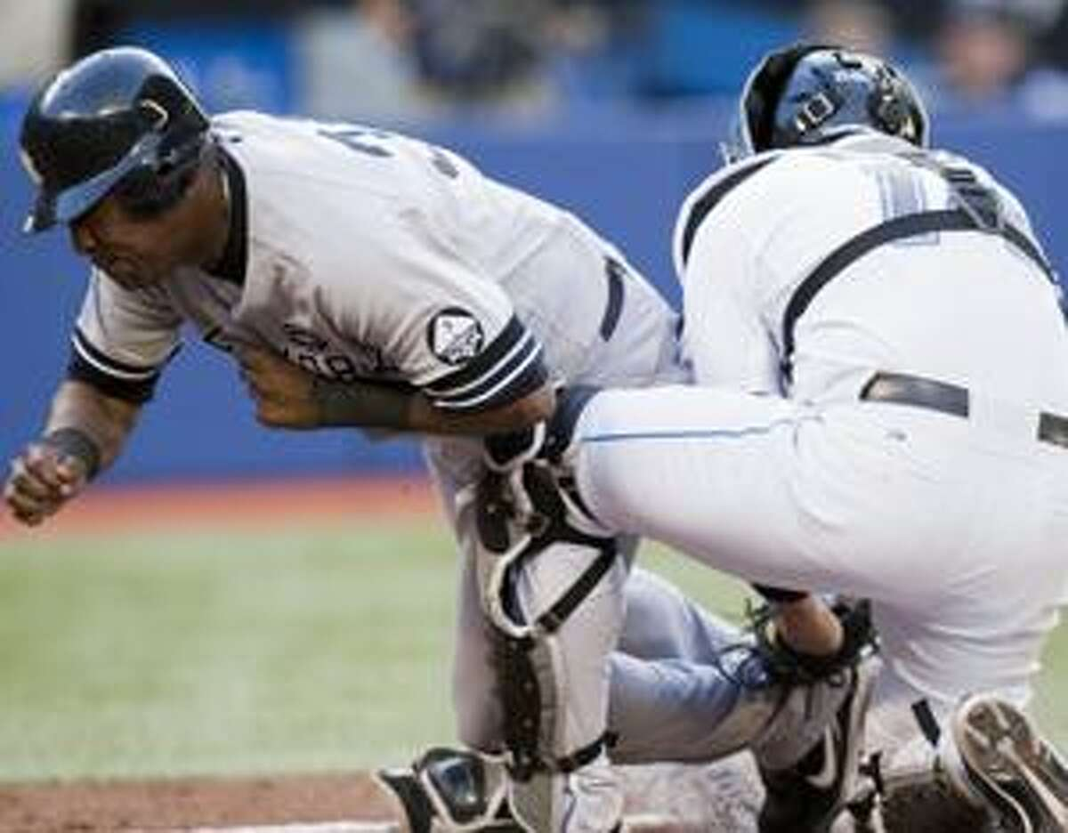 New York Yankees Marcus Thames, left, collides with Toronto Blue Jays catcher John Buck during second inning of their baseball in Toronto on Tuesday Aug. 24, 2010. Thames was out on the play. (AP Photo/The Canadian Press, Frank Gunn)
