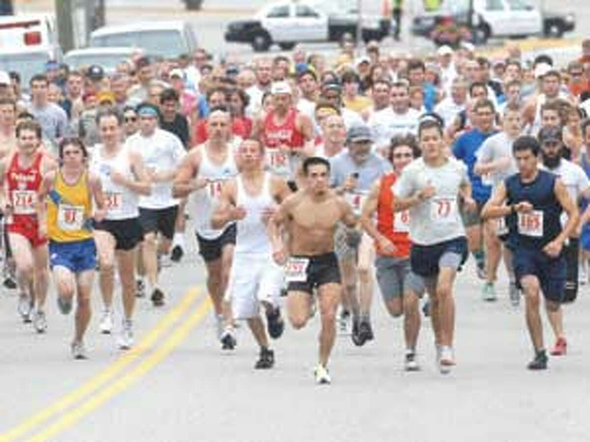 Runners make their way up New Litchfield Street at the start of the annual Torrington Road Race on Sunday.