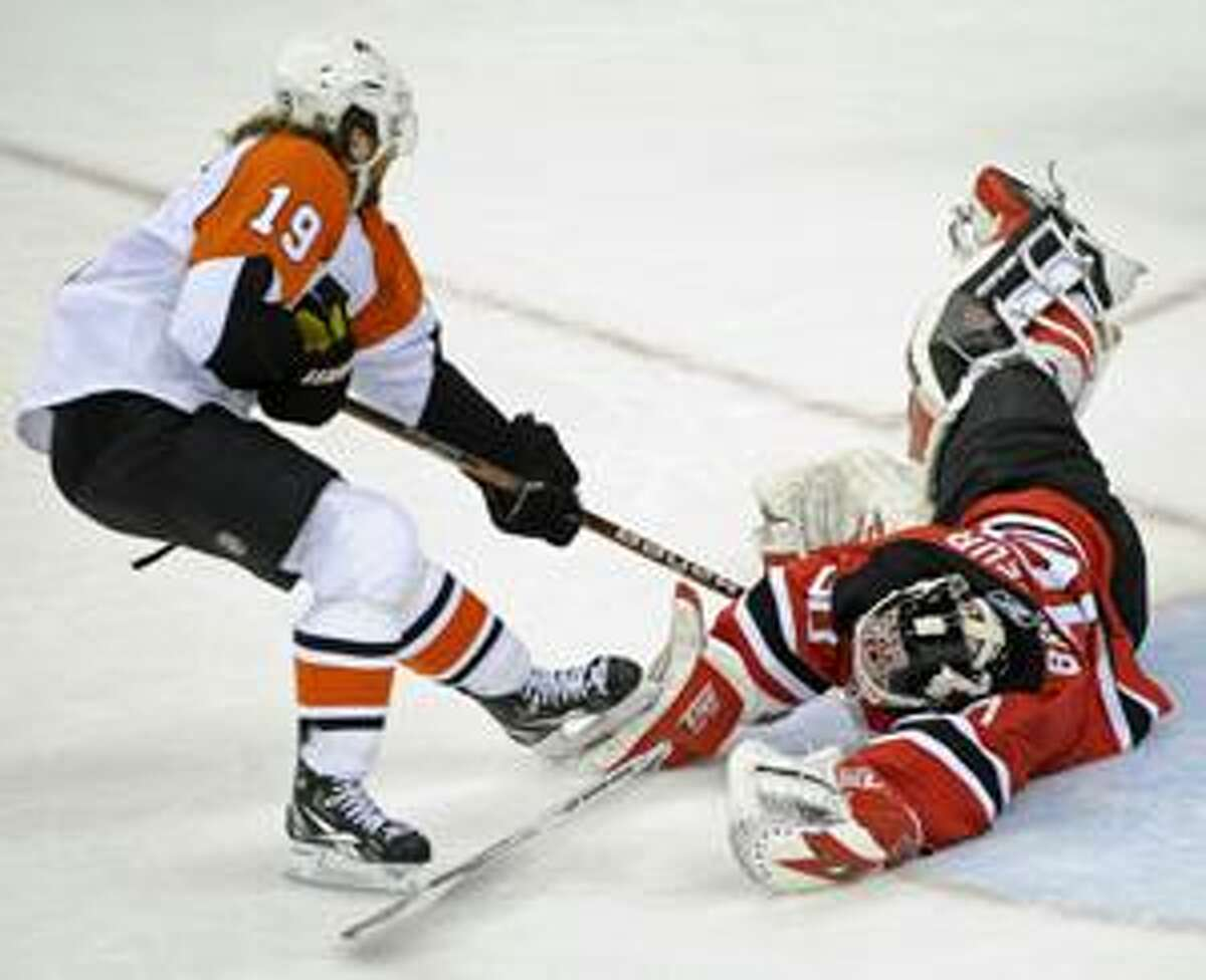 New Jersey Devils goaltender Martin Brodeur, right, makes a save on a shot by Philadelphia Flyers' Scott Hartnell during the second period of an NHL first-round playoff hockey game Friday, April 16, 2010 in Newark, N.J. (AP Photo/Bill Kostroun)