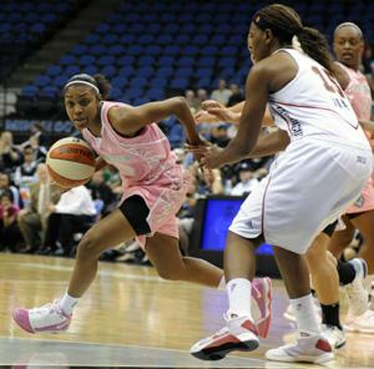 AP Minnesota Lynx's Renee Montgomery, left, breaks away from Connecticut Sun's Asjha Jones (15) during a WNBA game in Minneapolis on Friday. The Lynx wore pink jerseys, shorts and shoes as part of Breast Health Awareness Night.