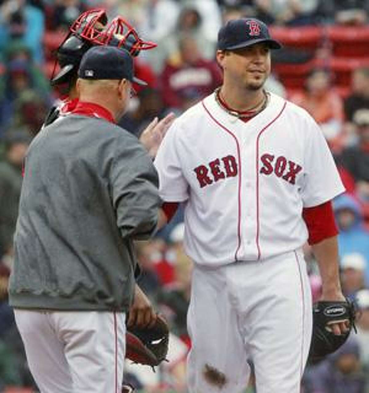 Boston Red Sox starter Josh Beckett, right, gets a pat on the back from manager Terry Francona after being replaced following a two-run home run by Seattle Mariners' Casey Kotchman during the seventh inning of their baseball game in Boston, Wednesday, Aug. 25, 2010. (AP Photo/Charles Krupa)