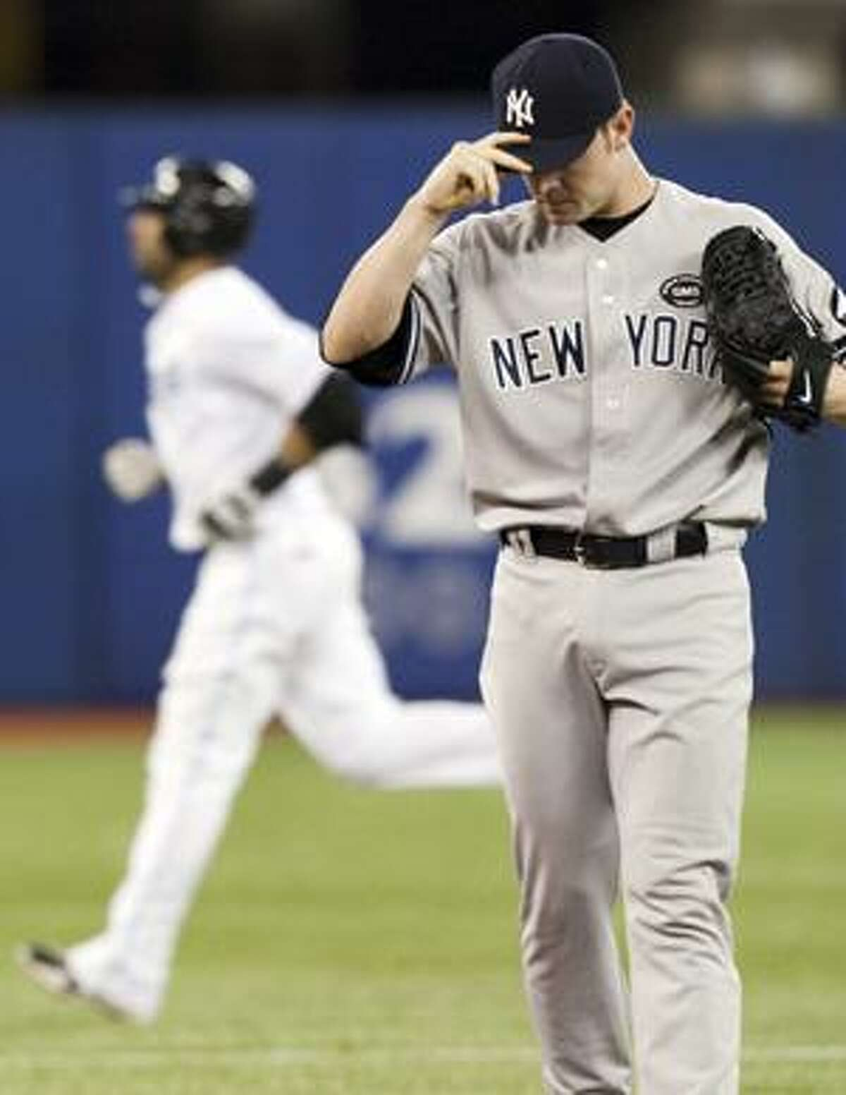 AP New York Yankees pitcher David Robertson hangs his head as Toronto Blue Jays Jose Bautista rounds the bases on his game-winning homer during the eighth inning of Monday's game in Toronto. The Blue Jays beat the Yankees 3-2.