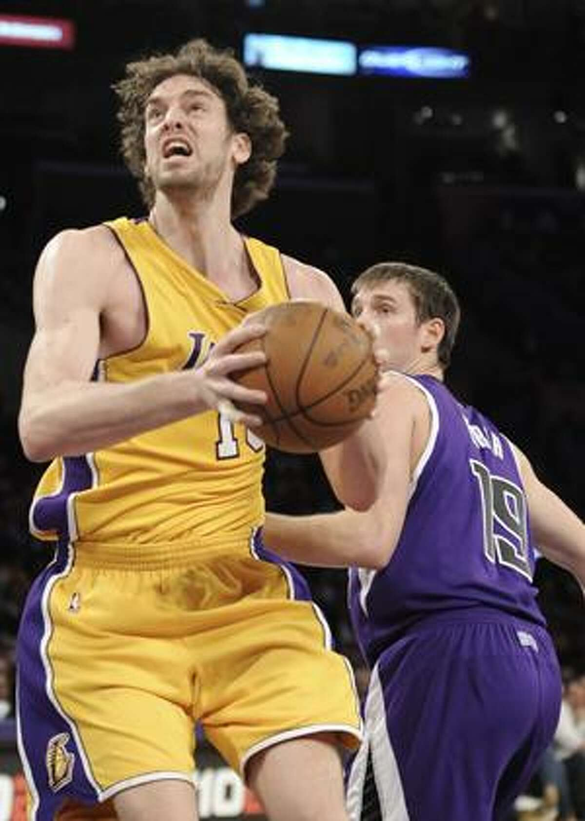 AP Los Angeles Lakers forward Pau Gasol, left, gets by Sacramento Kings guard Beno Udrih (19) for a basket in the first half of Tuesday's game in Los Angeles.