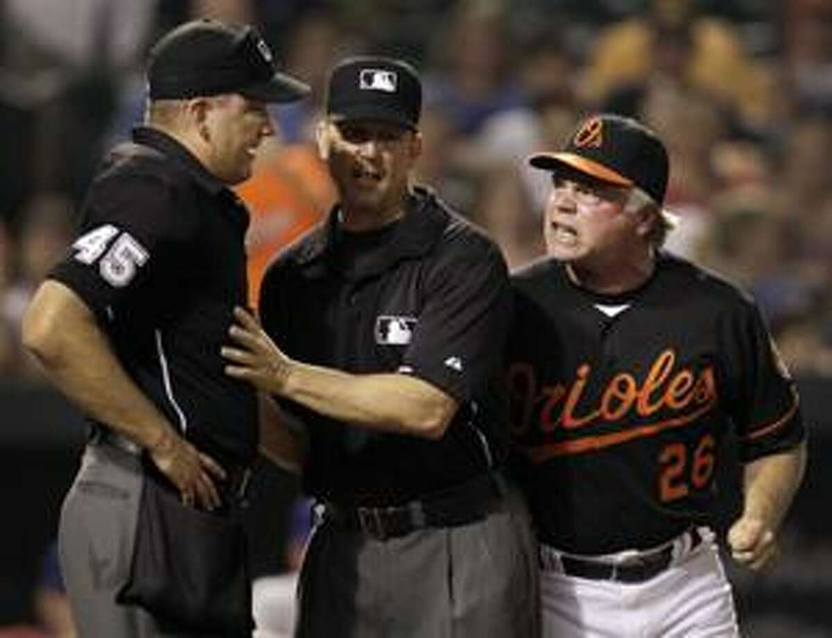 Baltimore Orioles manager Buck Showalter (26) is blocked by second base umpire Jeff Kellogg, center, after Showalter was ejected by home plate umpire Jeff Nelson (45) during the ninth inning of an Aug. 20 game in Baltimore. The Rangers won 2-0. (AP Photo/Rob Carr)
