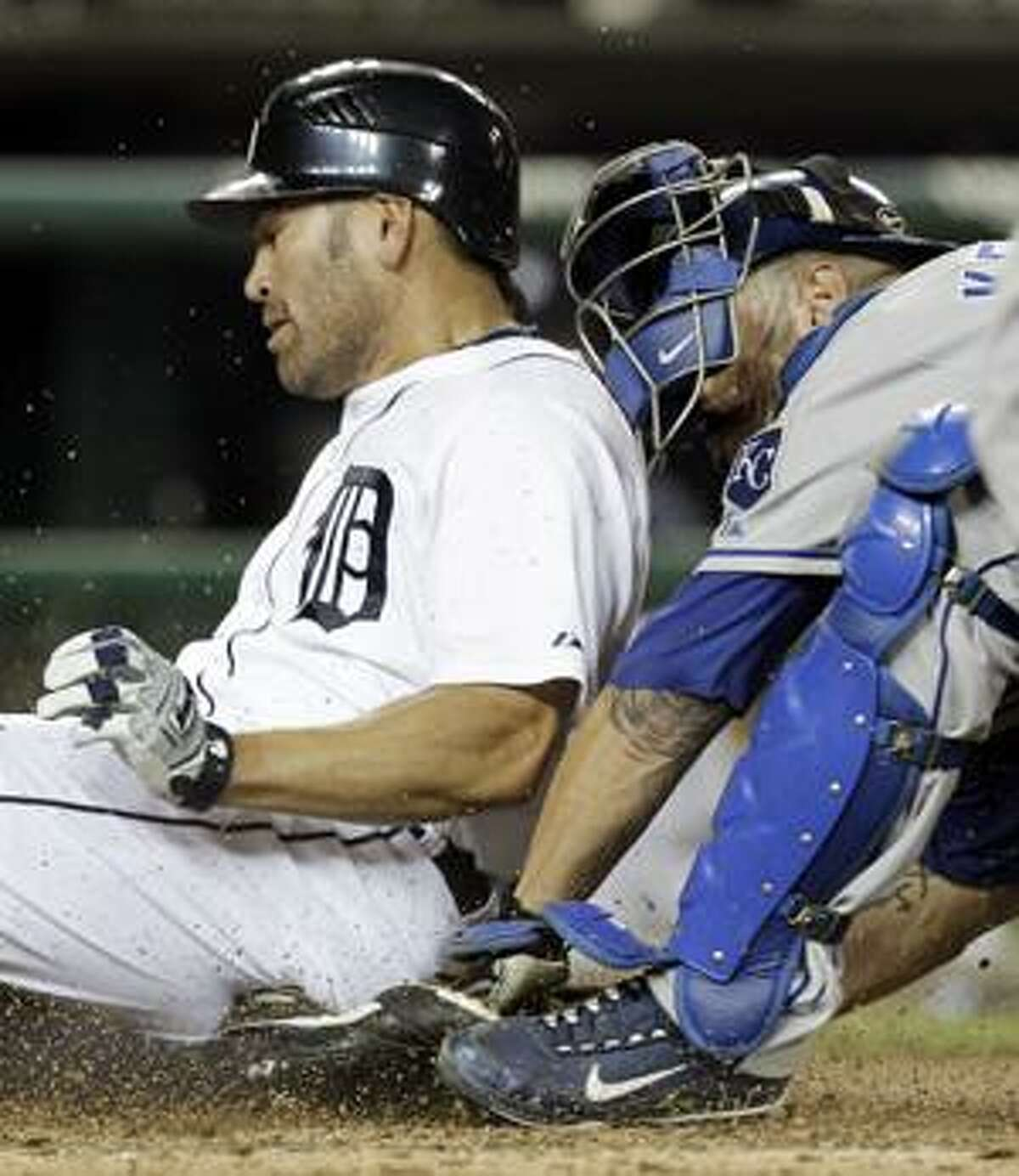 Johnny Damon of the Detroit Tigers, left, slides safely into home plate past the tag of Kansas City Royals catch Jason Kendall in the sixth inning of a baseball game in Detroit, Monday, Aug. 23, 2010. (AP Photo/Paul Sancya)