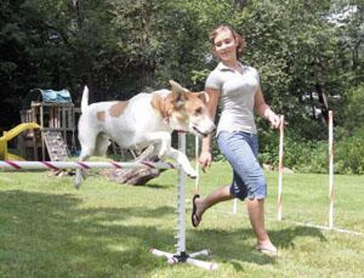 Katelyn Barber, 15 of Goshen, takes her dog Sherlock through the moves in her backyard Thursday.
