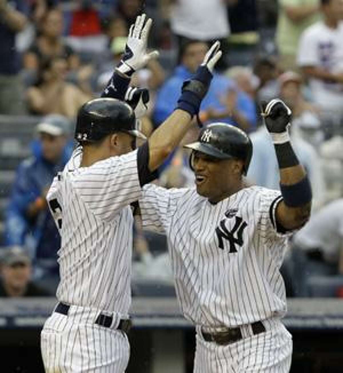 New York Yankees' Derek Jeter, left, greets teammate Robinson Cano, right, at the plate after Cano's fifth-inning grand slam off Seattle Mariners starting pitcher Luke French during a baseball game at Yankee Stadium on Sunday, Aug. 22, 2010, in New York. (AP Photo/Kathy Willens)