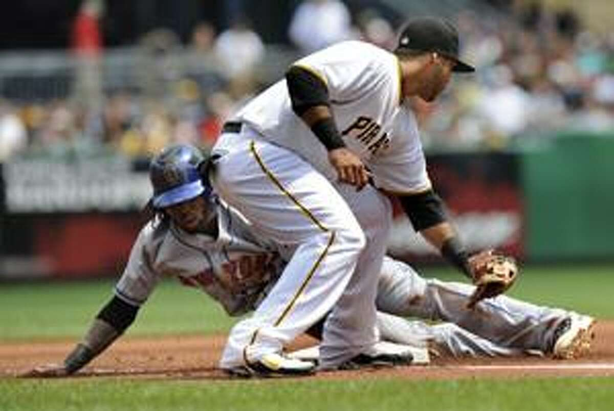 New York Mets' Jose Reyes, left, steals third base as Pittsburgh Pirates third baseman Pedro Alverez tries to make the tag during during the first inning of a baseball game Sunday, Aug. 22, 2010, in Pittsburgh. The Pirates have set a record with 18 consecutive losing seasons. Still, the team turned a profit in 2007, '08 and '09. (AP Photo/Don Wright)