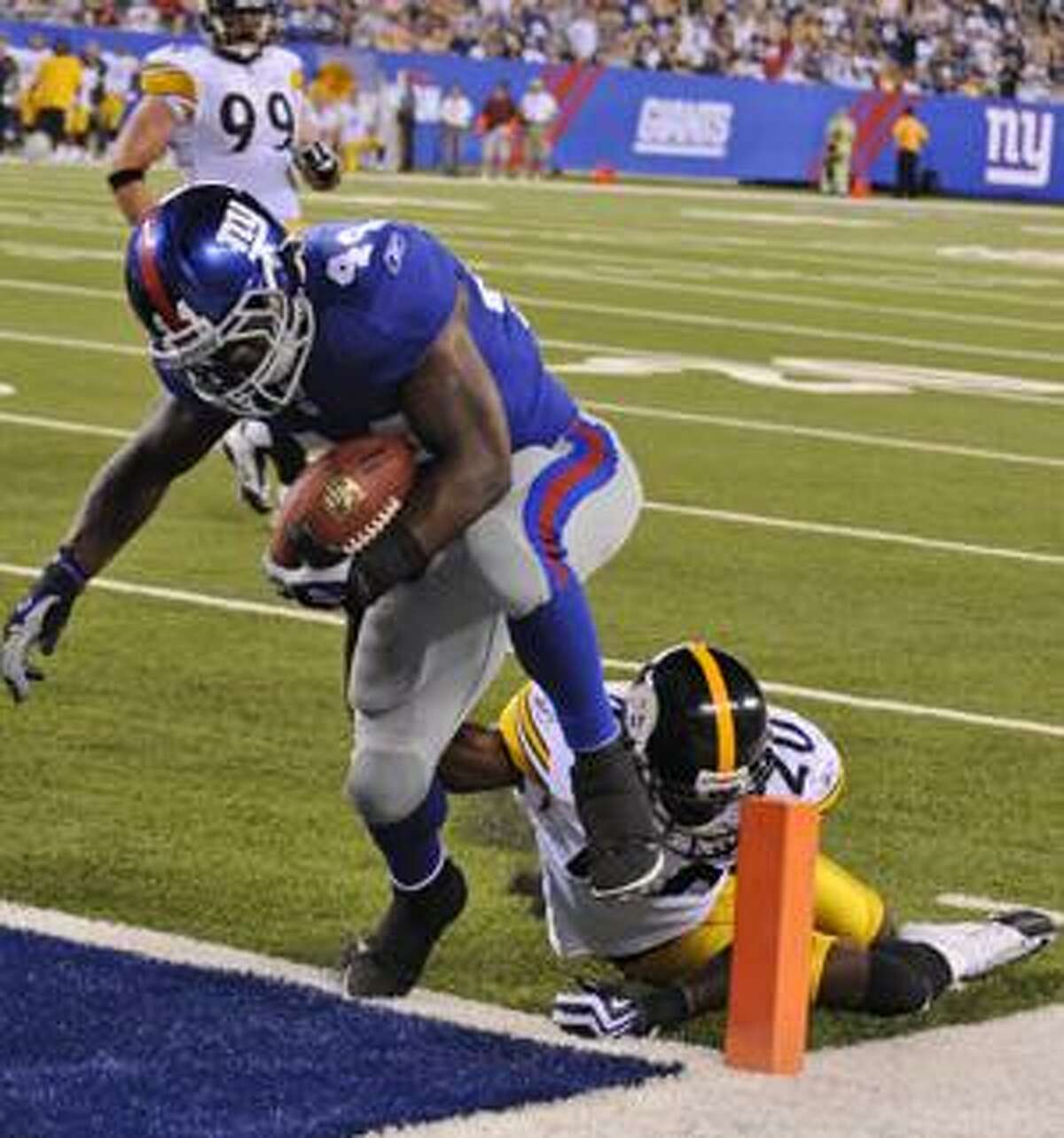 New York Giants running back Ahmad Bradshaw, right, breaks a tackle by Pittsburgh Steelers cornerback Bryant McFadden to score a touchdown during the second quarter of a preseason NFL football game at New Meadowlands Stadium in East Rutherford, N.J., Saturday, Aug. 21, 2010. (AP Photo/Bill Kostroun)