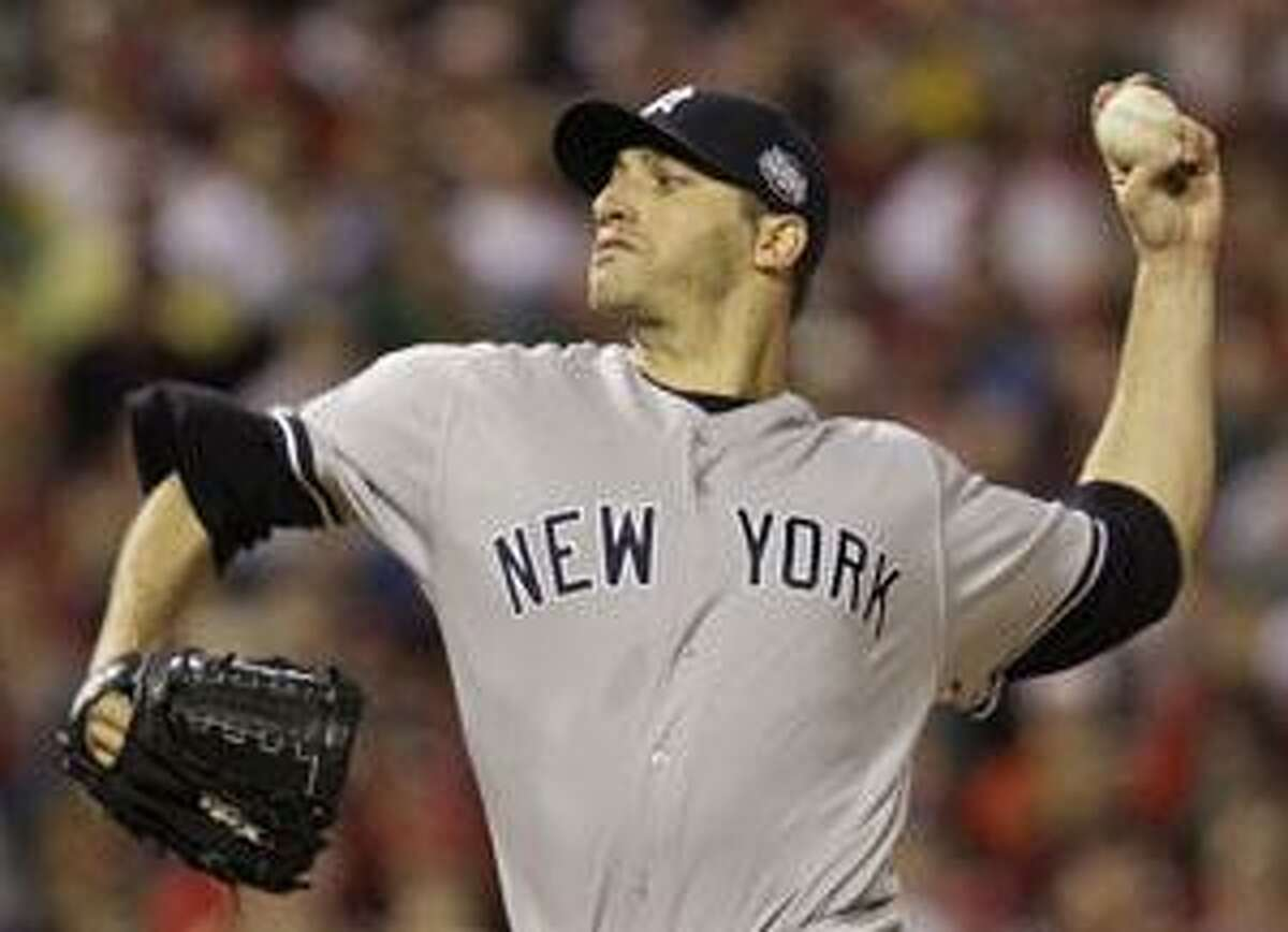 This is an Oct. 31 file photo showing New York Yankees' Andy Pettitte pitching against the Philadelphia Phillies during the first inning of Game 3 of the World Series in Philadelphia. Pettitte is staying with the New York Yankees, agreeing to an $11.75 million, one-year contract.
