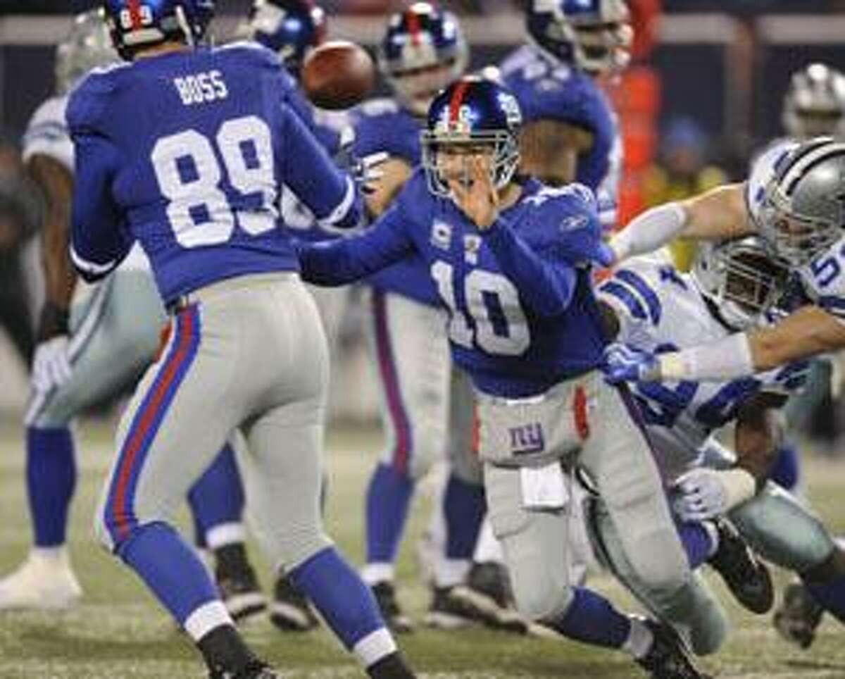 New York Giants quarterback Eli Manning (10), right, throws the ball to tight end Kevin Boss (89), for a 16-yard first down during the second quarter against the Dallas Cowboys Sunday at Giants Stadium in East Rutherford, N.J.