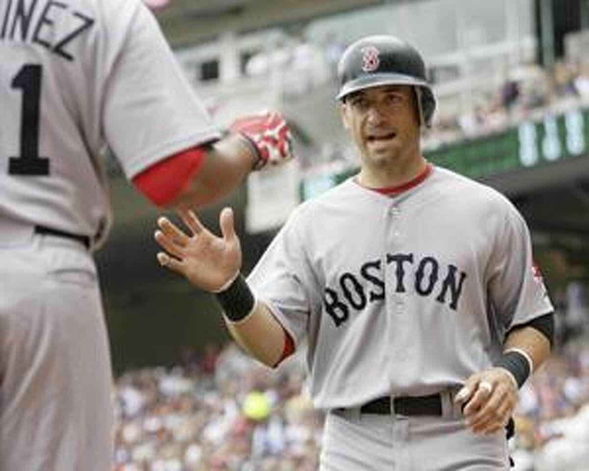 Boston Red Sox' Marcho Scutaro, right, is congratulated by teammate Victor Martinez after Scutaro scored in the first inning against the Minnesota Twins in the first inning of their baseball game Wednesday, April 14, 2010 in Minneapolis.(AP Photo/Andy King)