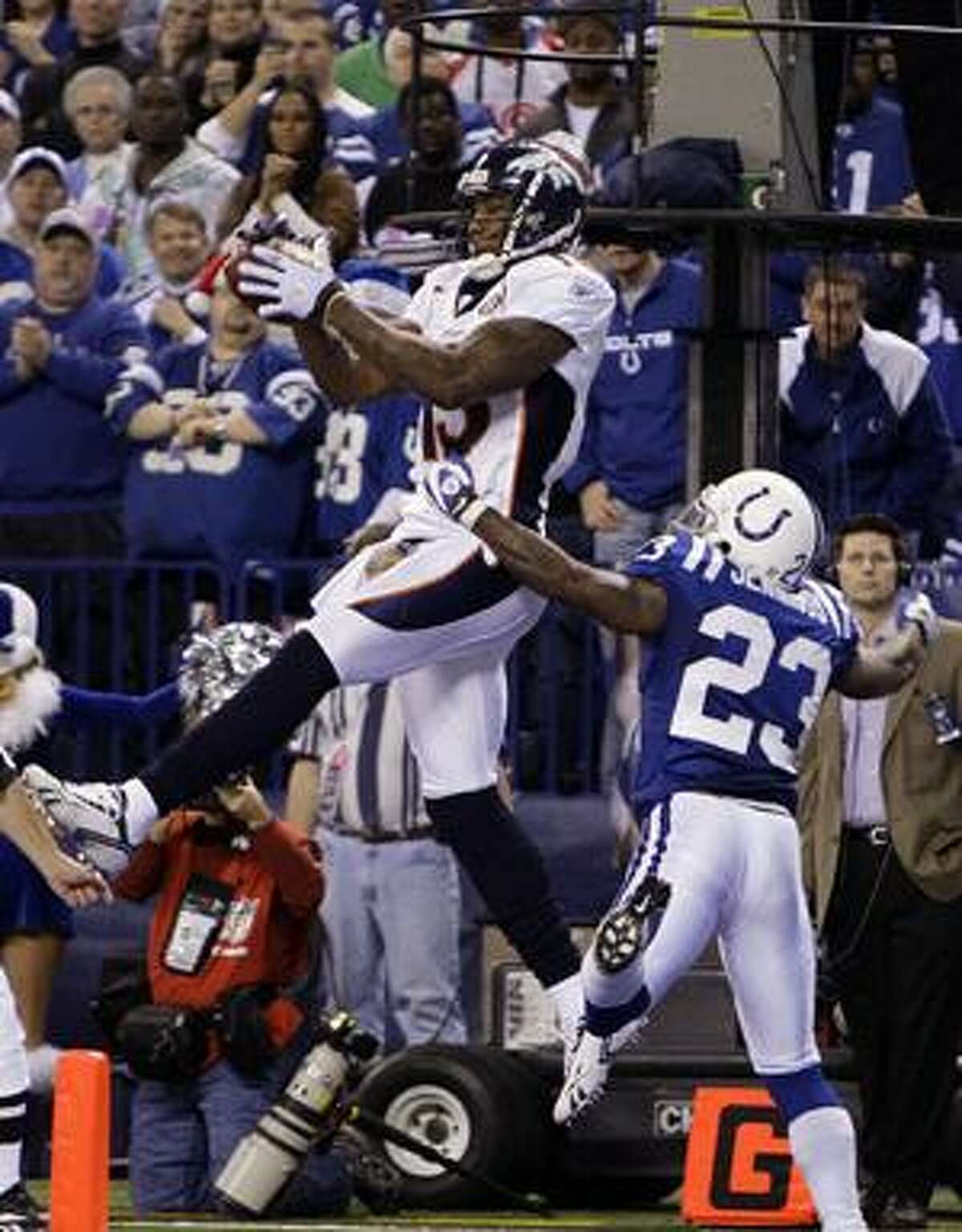 FILE - This Dec. 13, 2009, file photo, shows Denver Broncos wide receiver Brandon Marshall, left, catching a pass over Indianapolis Colts safety Tim Jennings for a touchdown in the fourth quarter of an NFL football game in Indianapolis. A person familiar with the deal says the Denver Broncos are trading Pro Bowl wide receiver Brandon Marshall to the Miami Dolphins for a pair of second-round draft picks. Marshall will fly to Miami on Wednesday, April 14, 2010, for a physical, said the person, who spoke on condition of anonymity because the teams hadn't announced the deal. (AP Photo/Michael Conroy)