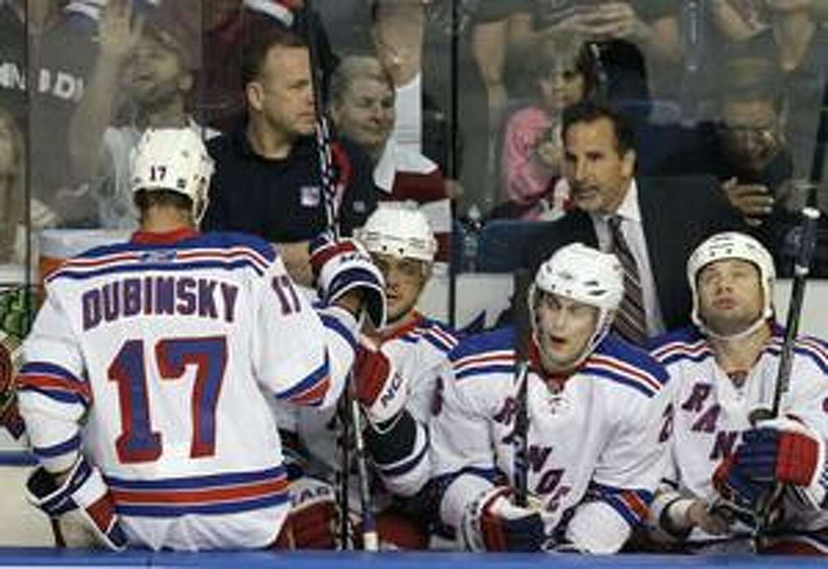 New York Rangers head coach John Tortorella, standing right, congratulates Brandon Dubinsky (17) on his first-period goal against the Tampa Bay Lightning in an NHL hockey game Friday, April 2, 2010, in Tampa, Fla. (AP Photo/Chris O'Meara)