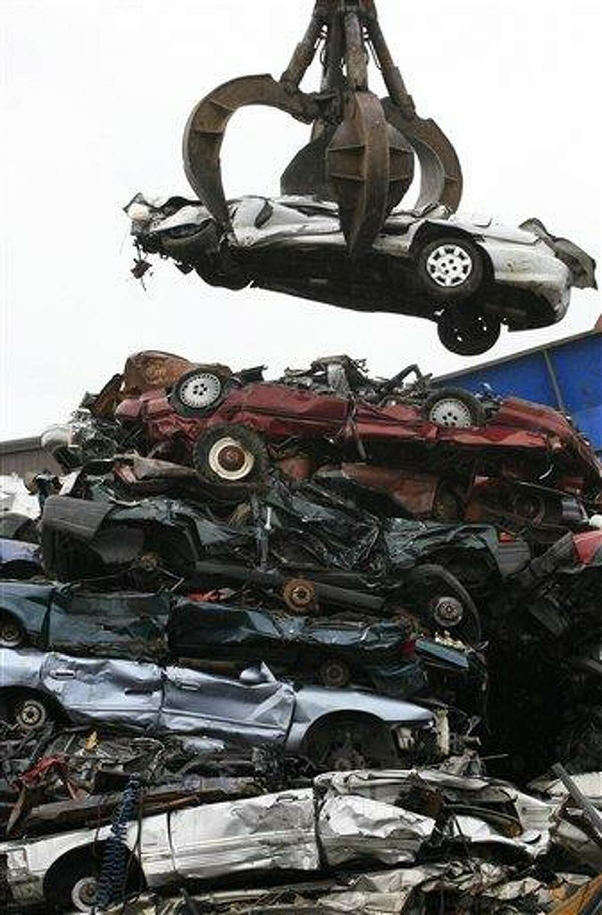 A crane lifts a flattened car from a stack of similar vehicles to a shredder at Gershow Recycling Corp. in Medford, N.Y., Thursday, Aug. 6, 2009. Many of the scrapped vehicles are part of the