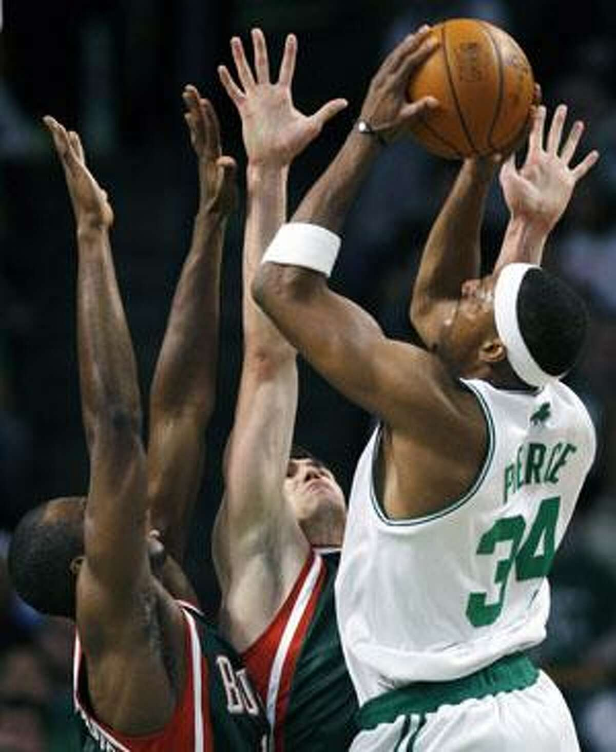 Boston Celtics' Paul Pierce (34) shoots over Milwaukee Bucks' Luc Mbah a Moute, left, and Ersan Ilyasova during the first quarter Tuesday in Boston.