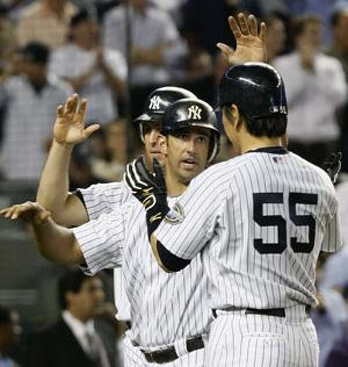 New York Yankees' Jorge Posada, center, greets Hideki Matsui (55) at the plate after Mark Teixeira, left, and Matsui scored on Posada's fourth-inning home run off Boston Red Sox pitcher Billy Traber at Yankee Stadium in New York, Thursday.