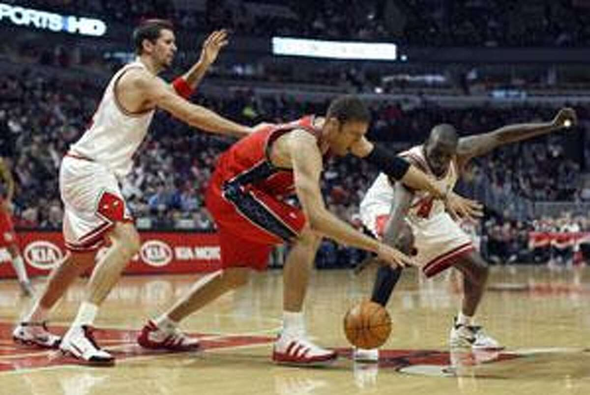 Chicago Bulls' Brad Miller and Luol Deng fight for the ball with the New Jersey Nets' Brook Lopez, center, during the first half Tuesday in Chicago.
