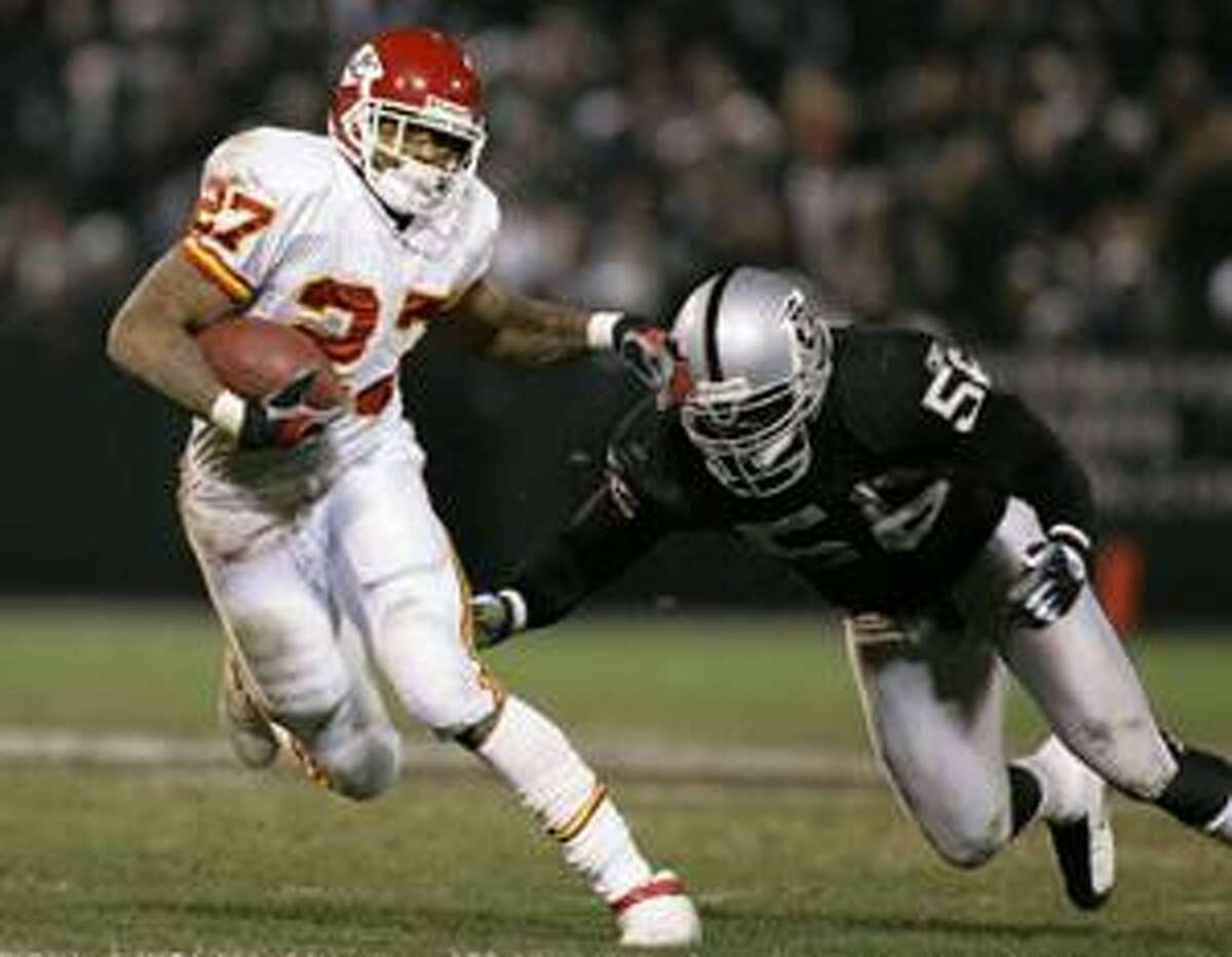 In this Dec. 23, 2006, file photo, Kansas City Chiefs' Larry Johnson, left, runs past Oakland Raiders' Derrick Burgess during a game in Oakland, Calif. The New England Patriots have obtained two-time Pro Bowl defensive end Burgess. Burgess had held out of training camp with the Raiders in hopes of being traded. On Thursday they obtained undisclosed draft considerations for him. The Patriots released offensive lineman Al Johnson.