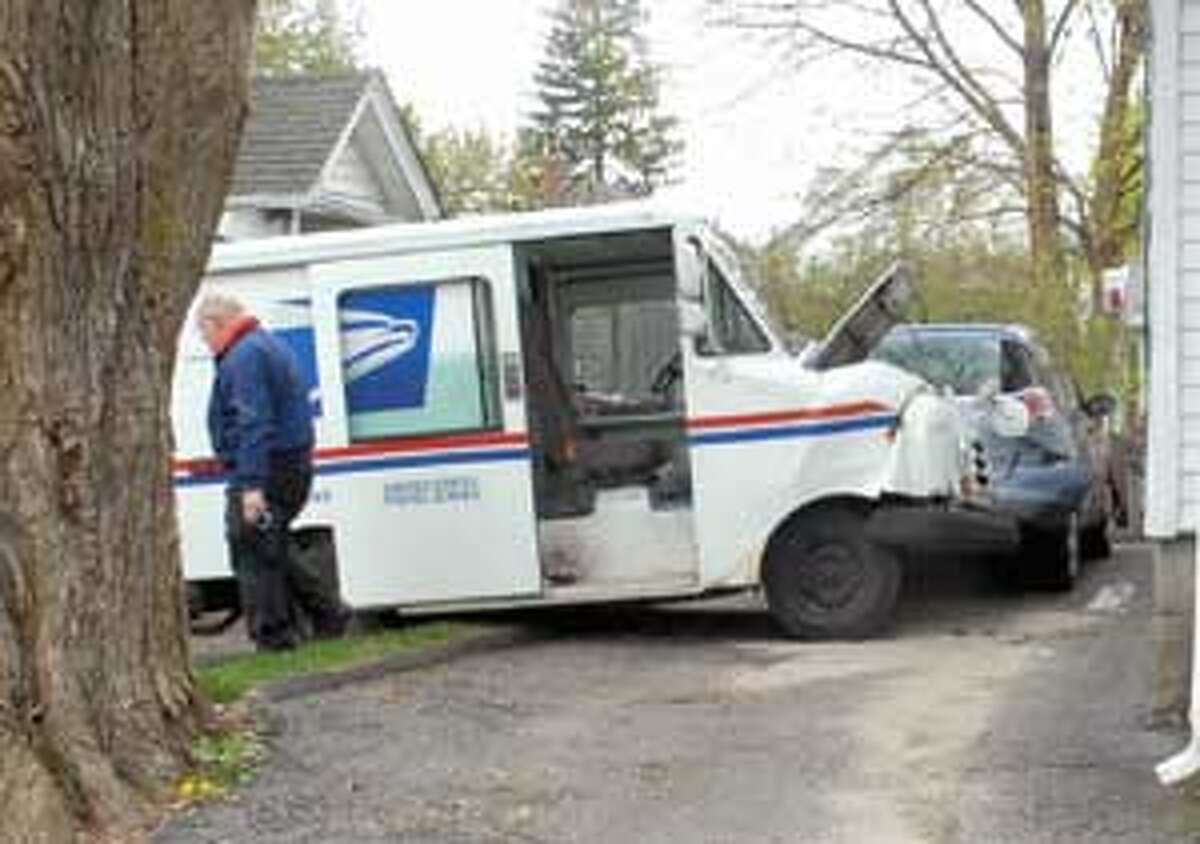 A U.S. Postal employee was transported to the hospital after his vehicle veered off of King Street in Torrington and collided with a parked car on Tuesday afternoon. Purchase a glossy print of this photo and more at www.registercitizen.com.