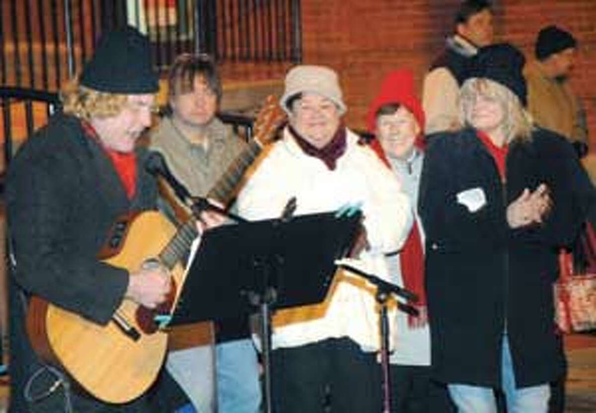 Guitarist Dino Pelletier and members of the North End Association lead the crowd in song during the annual carol sing and tree lighting event Sunday evening outside the Torrington Police Department.