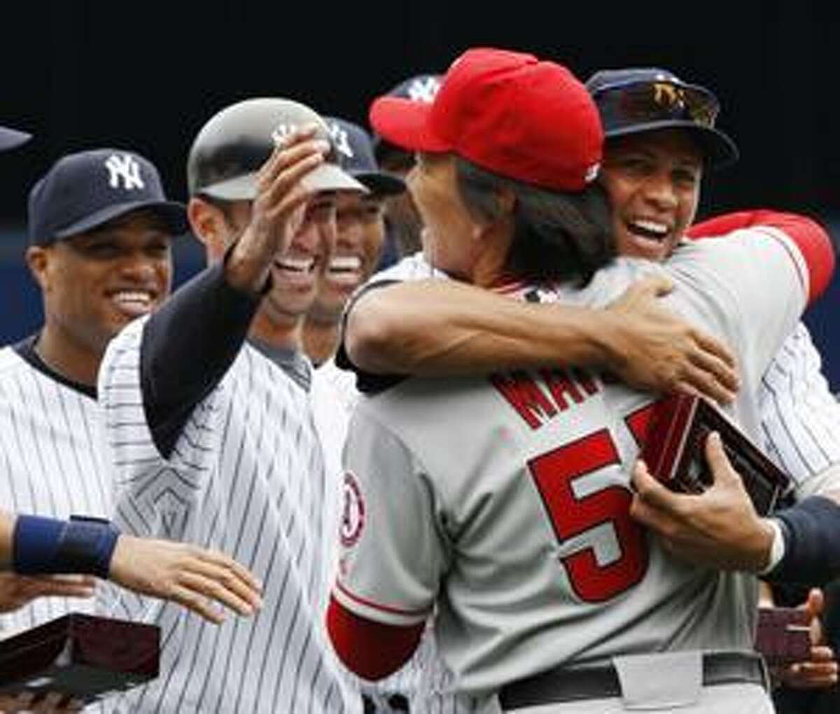 Los Angeles Angels' Hideki Matsui is embraced by former New York Yankees teammate Alex Rodriguez after Matsui received his 2009 World Series ring before their baseball game in New York on Tuesday, April 13, 2010. At left reaching out to Matsui is Yankees' Jorge Posada. (AP Photo/Kathy Willens)