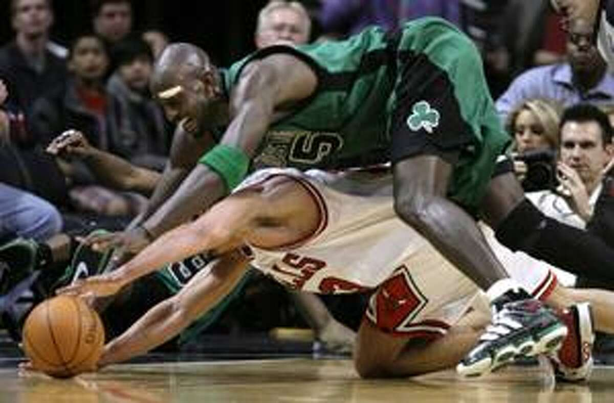 Boston Celtics forward Kevin Garnett falls onto Chicago Bulls center Joakim Noah as they both go for a loose ball during the third quarter of an NBA basketball game, Tuesday, April 13, 2010, in Chicago. (AP Photo/Charles Rex Arbogast)