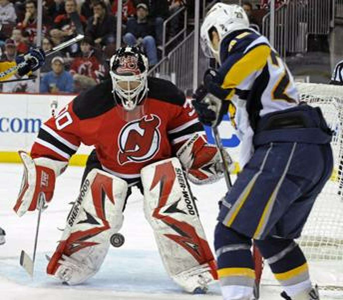 New Jersey Devils goaltender Martin Brodeur stops a shot from Buffalo Sabres' Jason Pominville, right, during the first period of an NHL hockey game Sunday, April 11, 2010 in Newark, N.J. (AP Photo/Bill Kostroun)