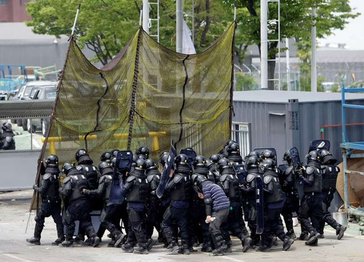Riot policemen with protective gear and net approach at the Ssangyong automaker's factory in Pyeongtaek, south of Seoul, South Korea, Thursday, July 23, 2009. Helicopters sprayed tear gas on militant auto workers using slingshots to shoot nuts and bolts at riot police Tuesday amid a tense labor dispute at the main factory of an ailing South Korean automaker. (AP Photo/ Lee Jin-man)