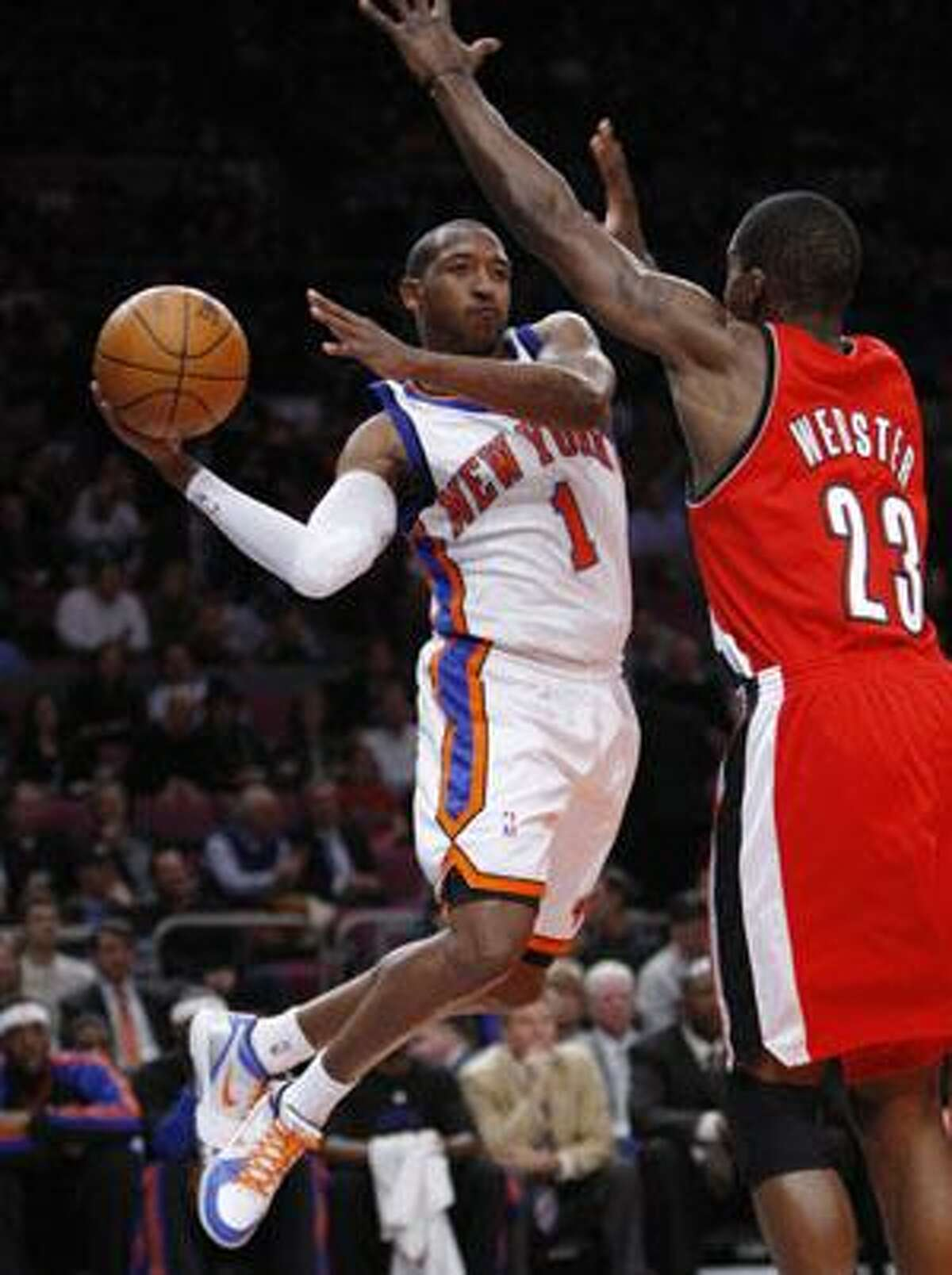New York Knicks guard Chris Duhon (1) passes around Portland Trail Blazers forward Martell Webster (23) during the first quarter Monday night at Madison Square Garden in New York.