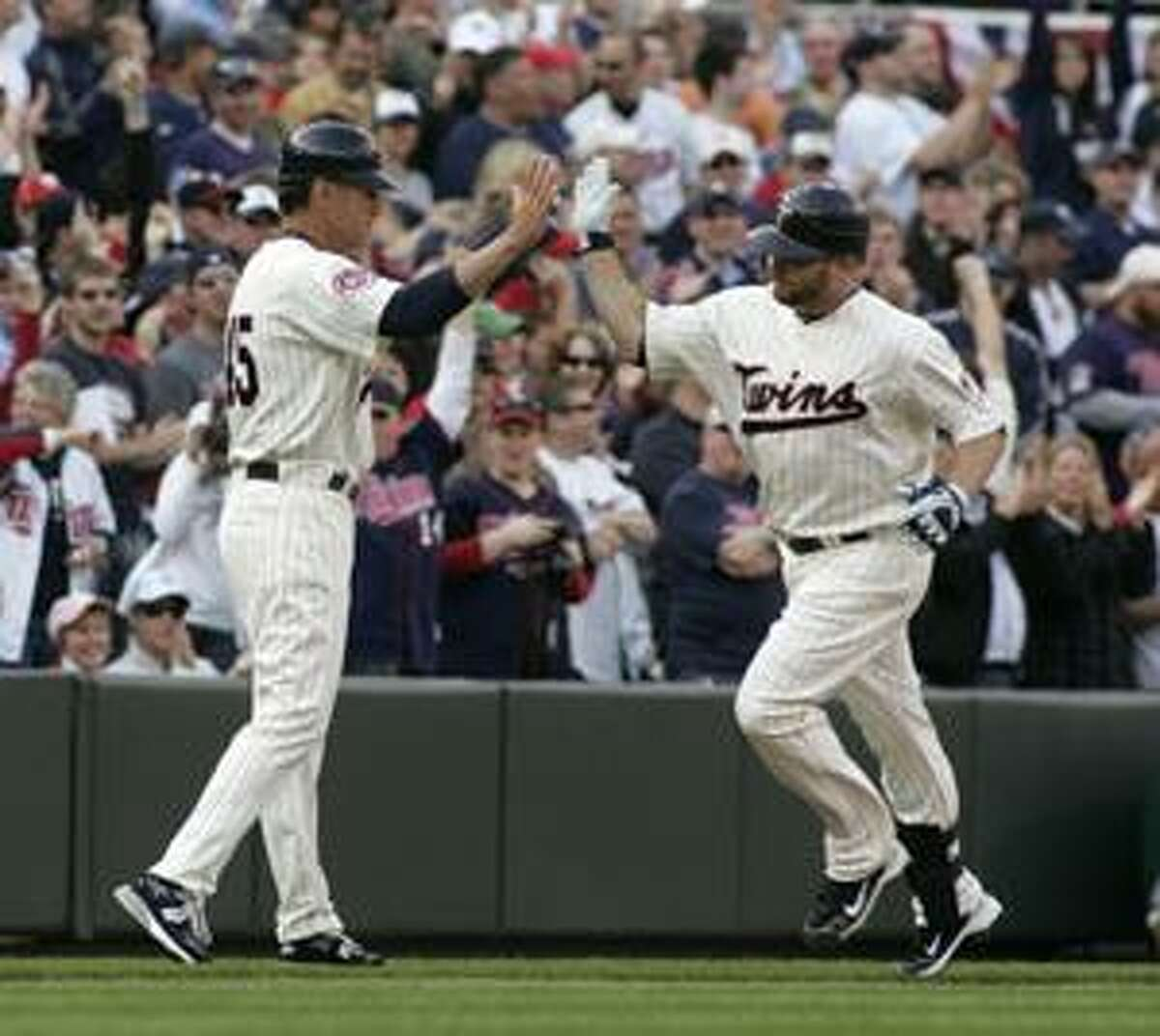 Minnesota Twins' Jason Kubel, right, is congratulated by third base coach Scott Ullger after hitting a solo home run during the seventh inning of the Twins' home opener baseball game against the Boston Red Sox, Monday, April 12, 2010 in Minneapolis. The Twins won 5-2. (AP Photo/Paul Battaglia)