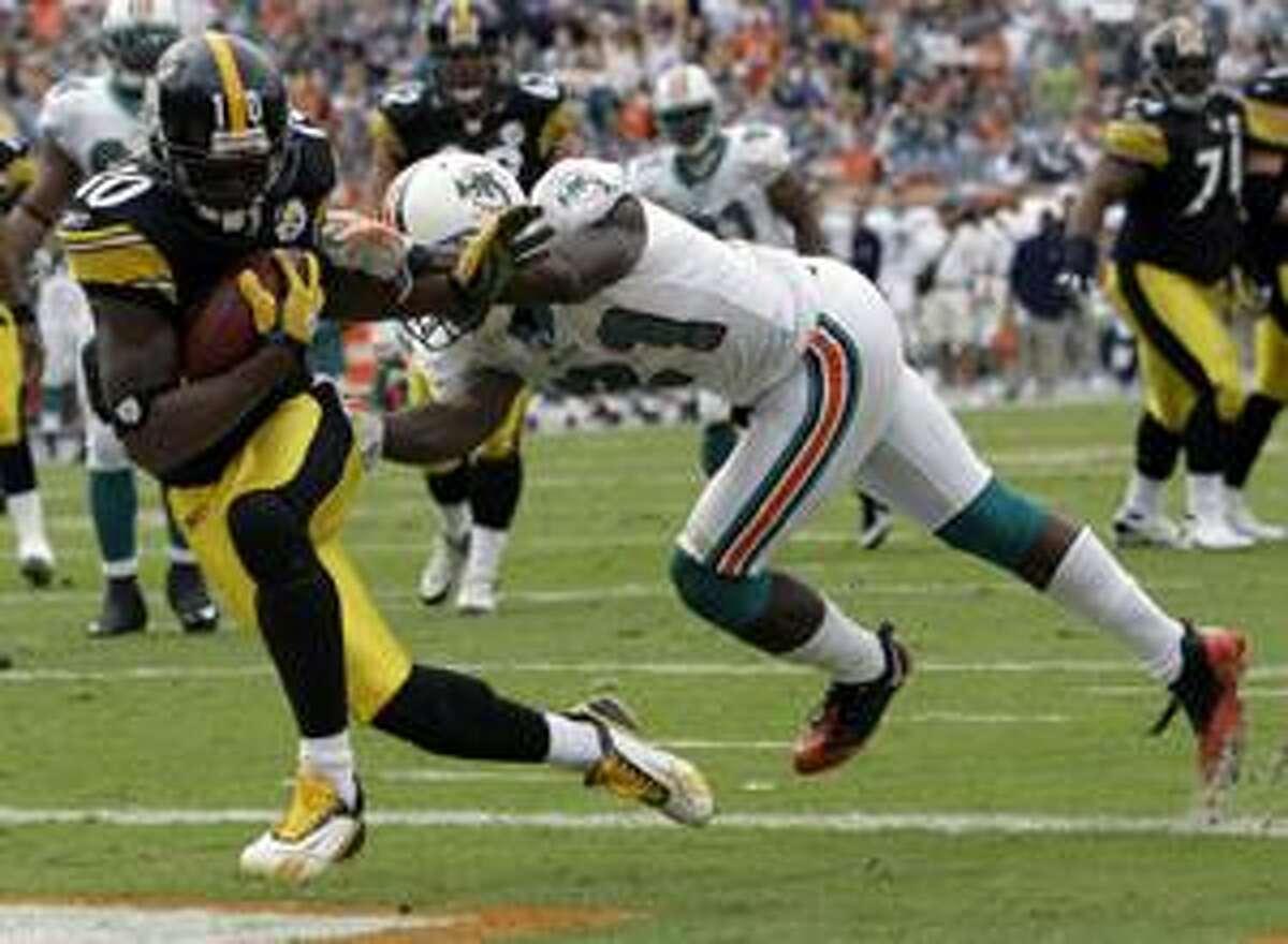 Pittsburgh Steelers wide receiver Santonio Holmes (10) eludes Miami Dolphins cornerback Vontae Davis to score a touchdown Jan. 3, 2010, in Miami. The New York Jets acquired Holmes from the Pittsburgh Steelers Sunday April 11, 2010(AP Photo/Lynne Sladky)