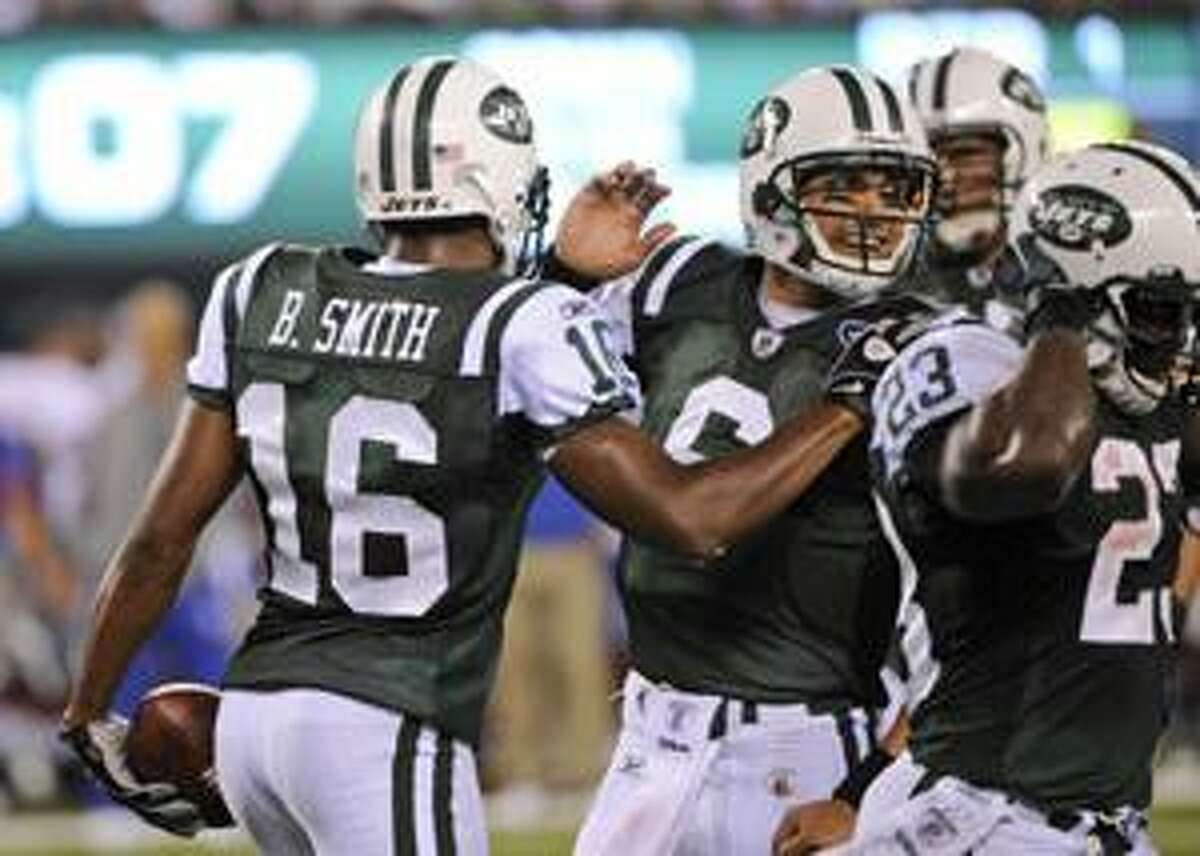 New York Jets quarterback Mark Sanchez celebrates with teammate Brad Smith, left, after Smith scored a touchdown during the first quarter of a preseason NFL football game against the New York Giants at New Meadowlands Stadium in East Rutherford, N.J., Monday, Aug. 16, 2010. (AP Photo/Bill Kostroun)