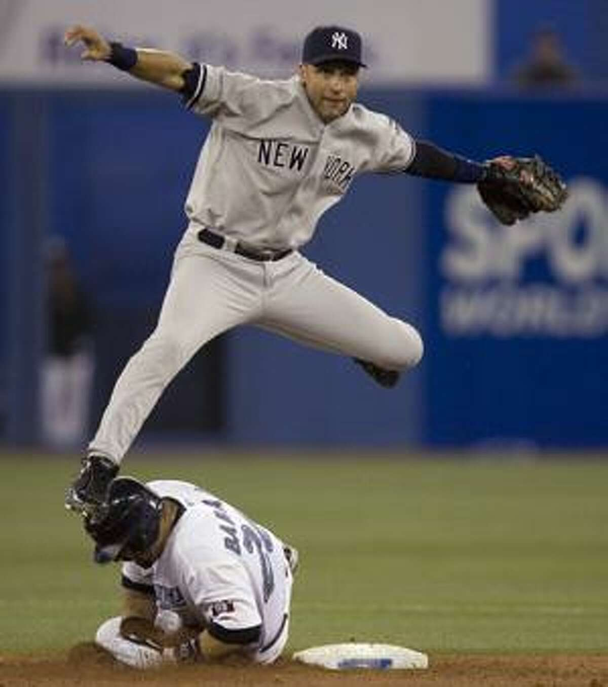 New York Yankees shortstop Derek Jeter leaps over Toronto Blue Jays' Rod Barajas at second base to turn a double play during the fifth inning Tuesday in Toronto. Jose Bautista was out at first.