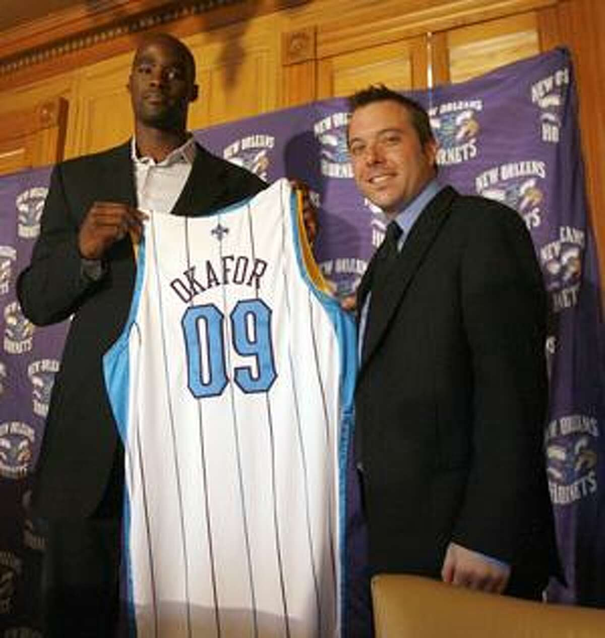 Emeka Okafor holds up his new jersey with New Orleans Hornets executive Chad Shinn, right, as he is introduced as the team's new center Tuesday in New Orleans.