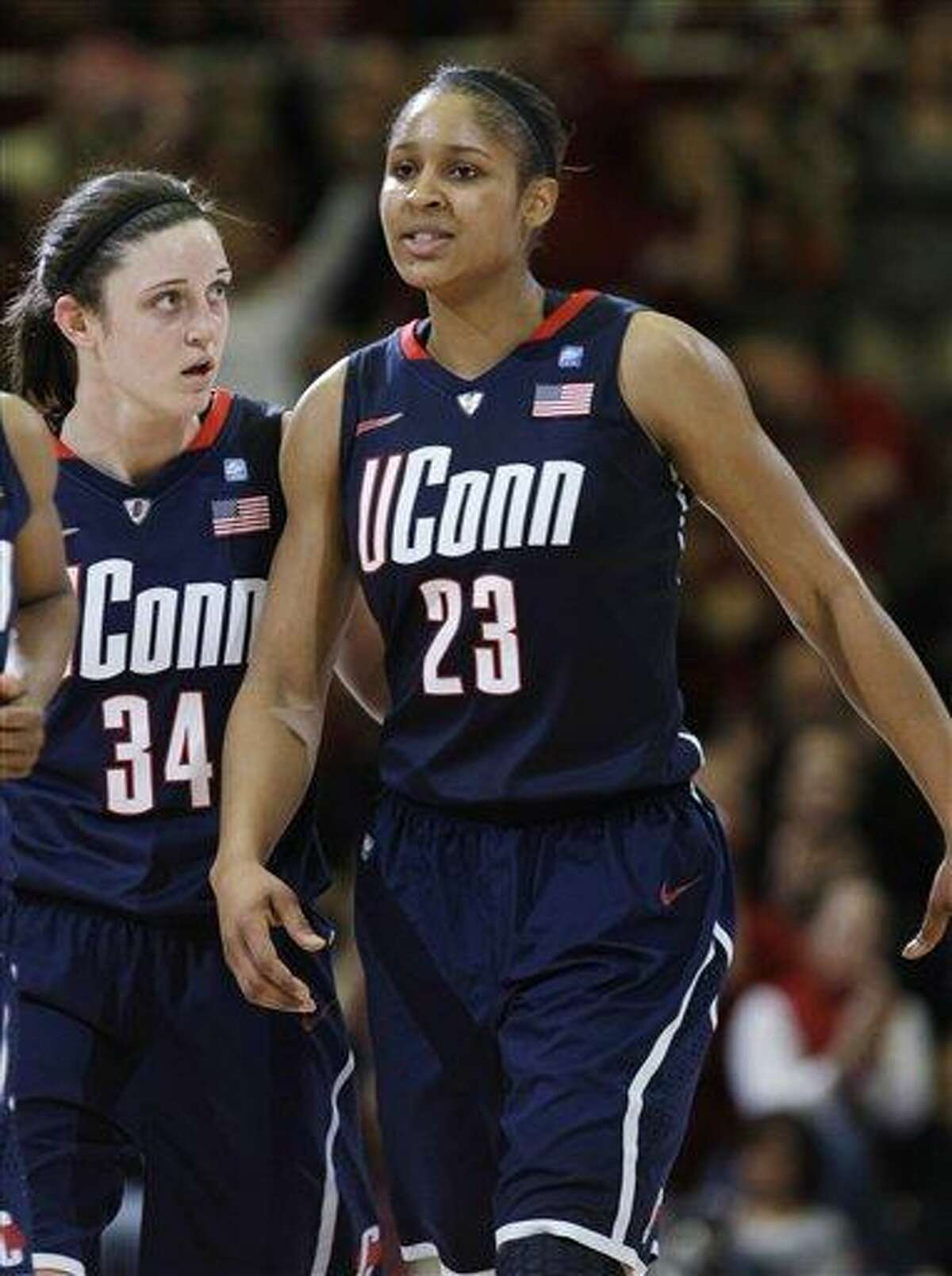 Connecticut forward Maya Moore (23) and guard Kelly Faris (34) walk to the bench in second half of an NCAA college basketball game against Stanford in Stanford, Calif., Thursday, Dec. 30, 2010. Stanford won 71-59, ending Connecticut's 90-game winning streak. (AP Photo/Paul Sakuma)