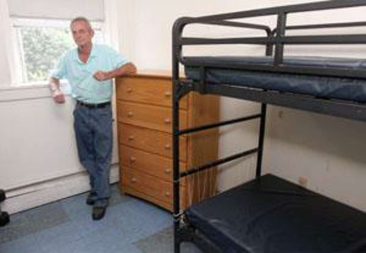 YMCA homeless shelter Director Bruce Mochan is seen at right in one of the shelter's rooms. Below is the shelter's common area.