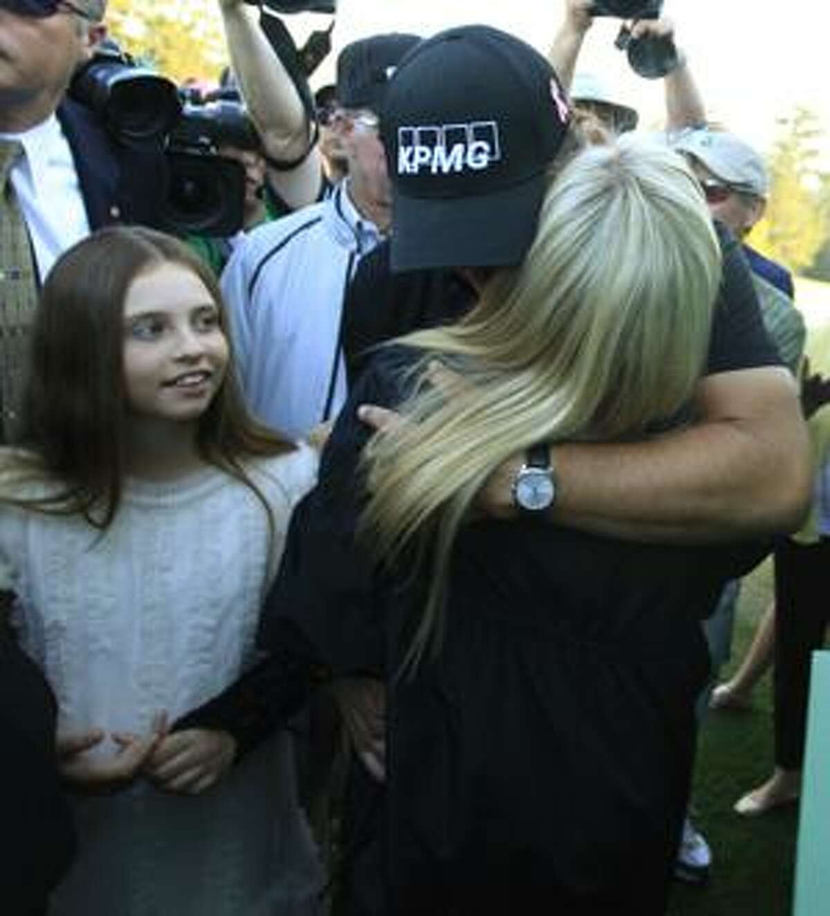 Daughter Amanda, left, watches as Phil Mickelson hugs his wife Amy after winning the Masters golf tournament in Augusta, Ga., Sunday. (AP Photo/Charlie Riedel)