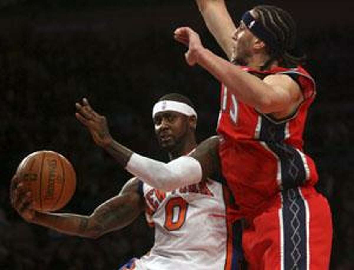 New York Knicks guard Larry Hughes (0) goes to the basket against New Jersey Nets center Josh Boone during the second quarter Sunday at Madison Square Garden in New York. The Knicks defeated the Nets 106-97.