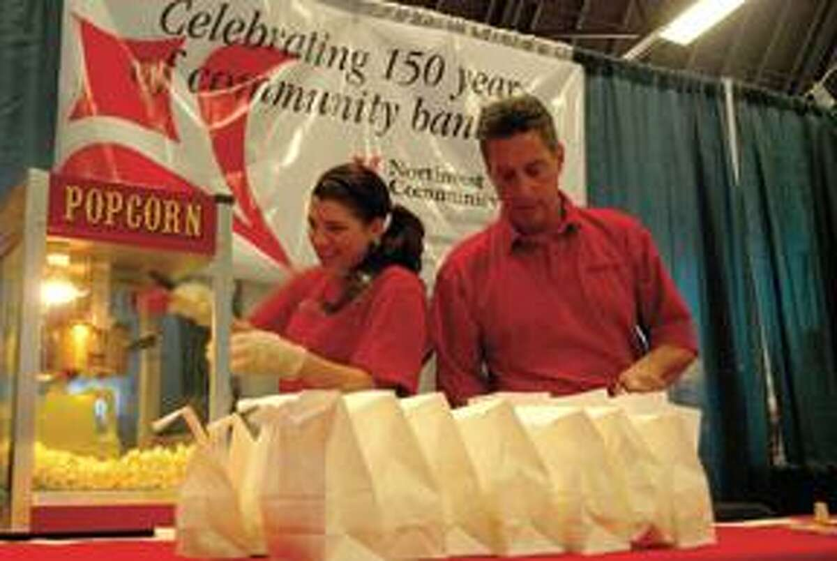 RONALD DEROSA/Register CitizenDanielle Pace and Alan Diulio, of Northwest Community Bank, prepare popcorn bags that were handed out during the 2010 Home and Business Expo in Torrington on Saturday.