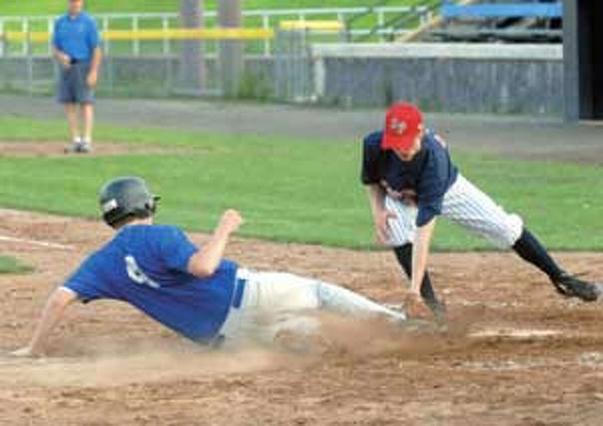 Winsted's Tyler Burrill slides safely into home ahead of the tag from Torrington's Austin Poucher during a four-run second inning Monday night at Fuessenich Park.