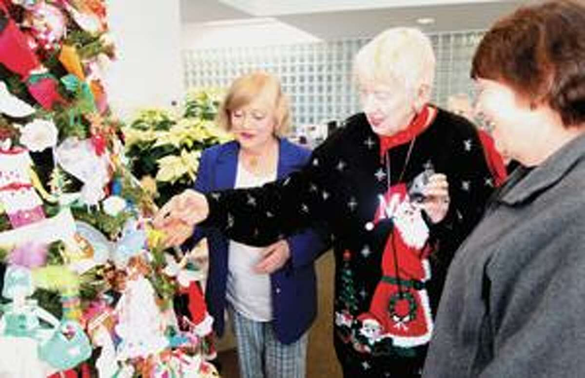 SONJA ZINKE/Register CitizenMary Gasser, center, shows off her handy work to friends and former co-workers from Rose Haven, left Jennifer Heym and Mary Nusom and others Friday at the Center for Cancer Care in Torrington. Mary crafted hundreds of ornaments for the tree that decorates the centers lobby. Purchase a glossy print of this photo and more at www.registercitizen.com