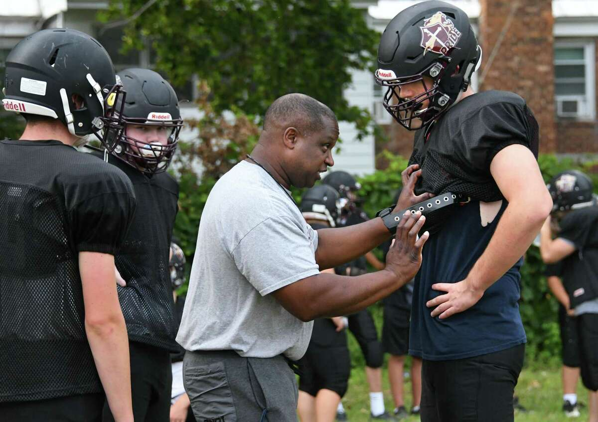 Holy Trinity assistant head coach William Headon demonstrates a move on senior tackle Liam Maloney, right, during practice at Bishop Gibbons High School on Monday, Aug. 28, 2017 in Schenectady, N.Y. Maloney is headed to play for UConn. (Lori Van Buren / Times Union)