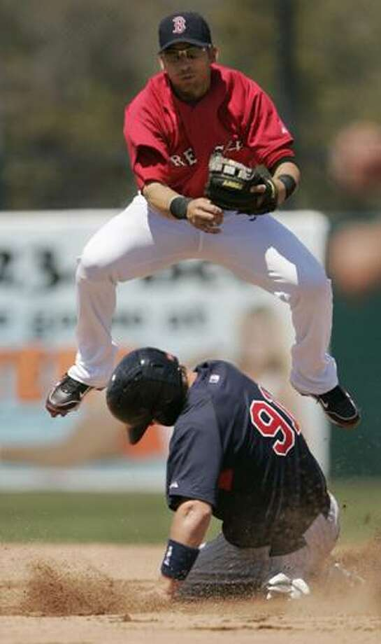 Minnesota Twins' Joe Benson slides out at second base as Boston Red Sox shortstop Marco Scutaro, top, throws to first to complete a double play in the fifth inning of a spring training baseball game, in Fort Myers, Fla., Thursday, April 1, 2010. The Red Sox defeated the Twins 5-3. (AP Photo/Steven Senne) Photo: ASSOCIATED PRESS / AP2010