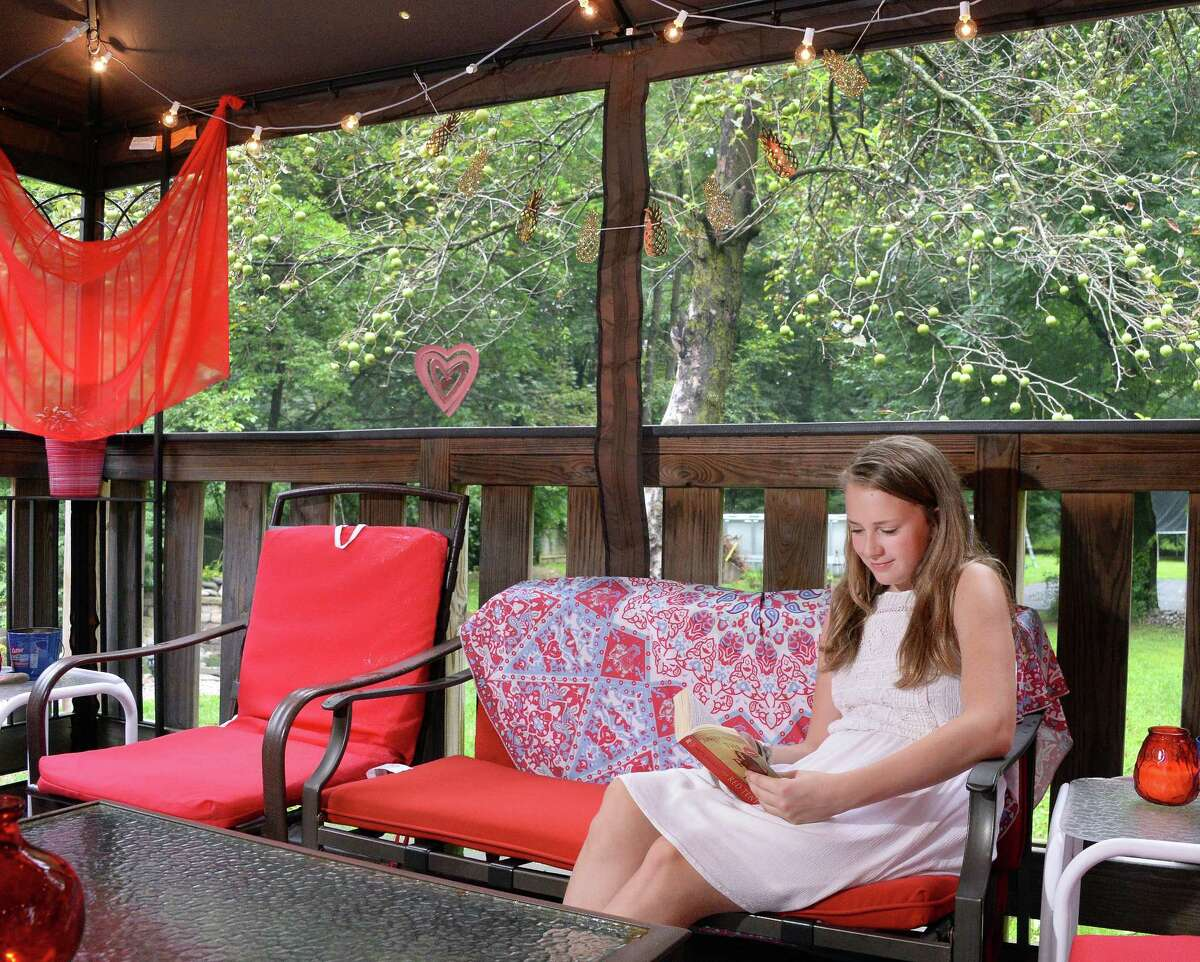 Eleven-year-old Britton Otis catches up on her summer reading in her backyard Friday August 18, 2017 in Glenville, NY. (John Carl D'Annibale / Times Union)
