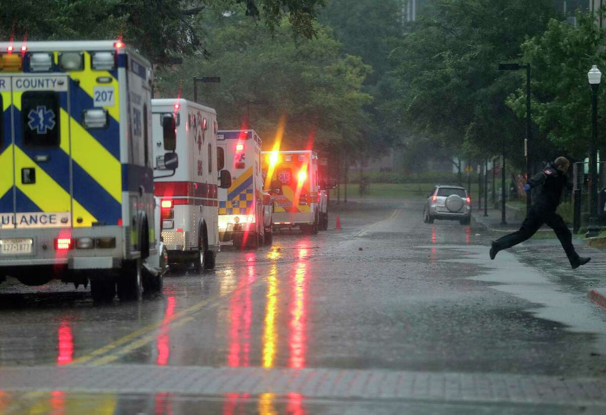 An EMT jumps over a puddle as ambulances line up to evacuate some ICU patients out of the Texas Medical Center as Harvey rains down.