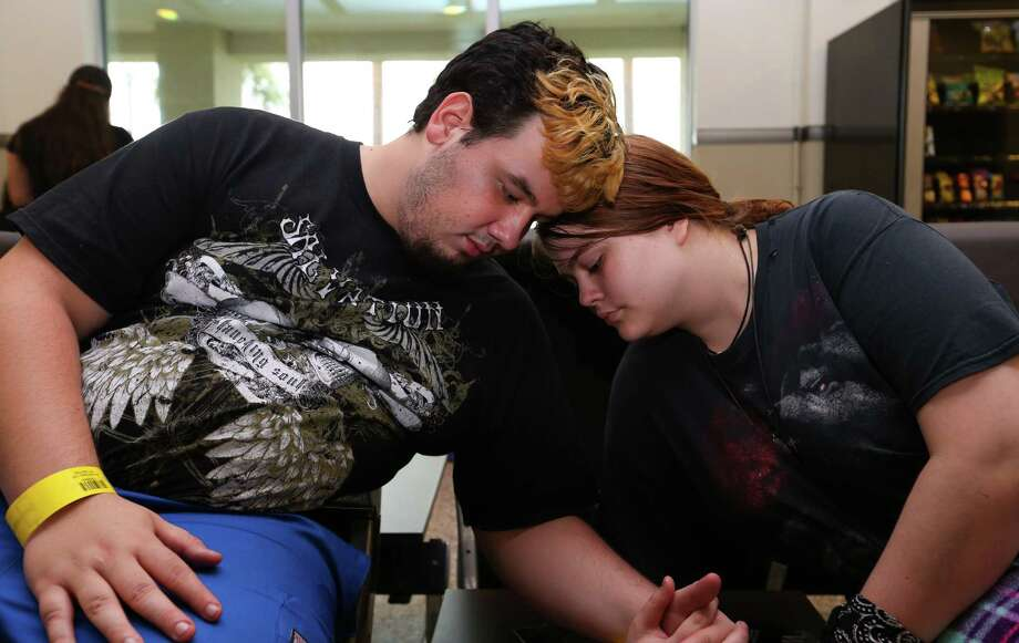 Dickinson flood evacuees Dylan Pankonien, from left, and girlfriend Kelli Morrow share a tender moment at Scholes International Airport while waiting to be airlifted to Dallas on Monday, August 28, 2017, in Galveston. Evacuees would be sent to other places by Texas Air National Guard after spent Sunday night at a shelter in Galveston. ( Yi-Chin Lee / Houston Chronicle) Photo: Yi-Chin Lee / Houston Chronicle, DickinsonEvacuees / Houston Chronicle 2017