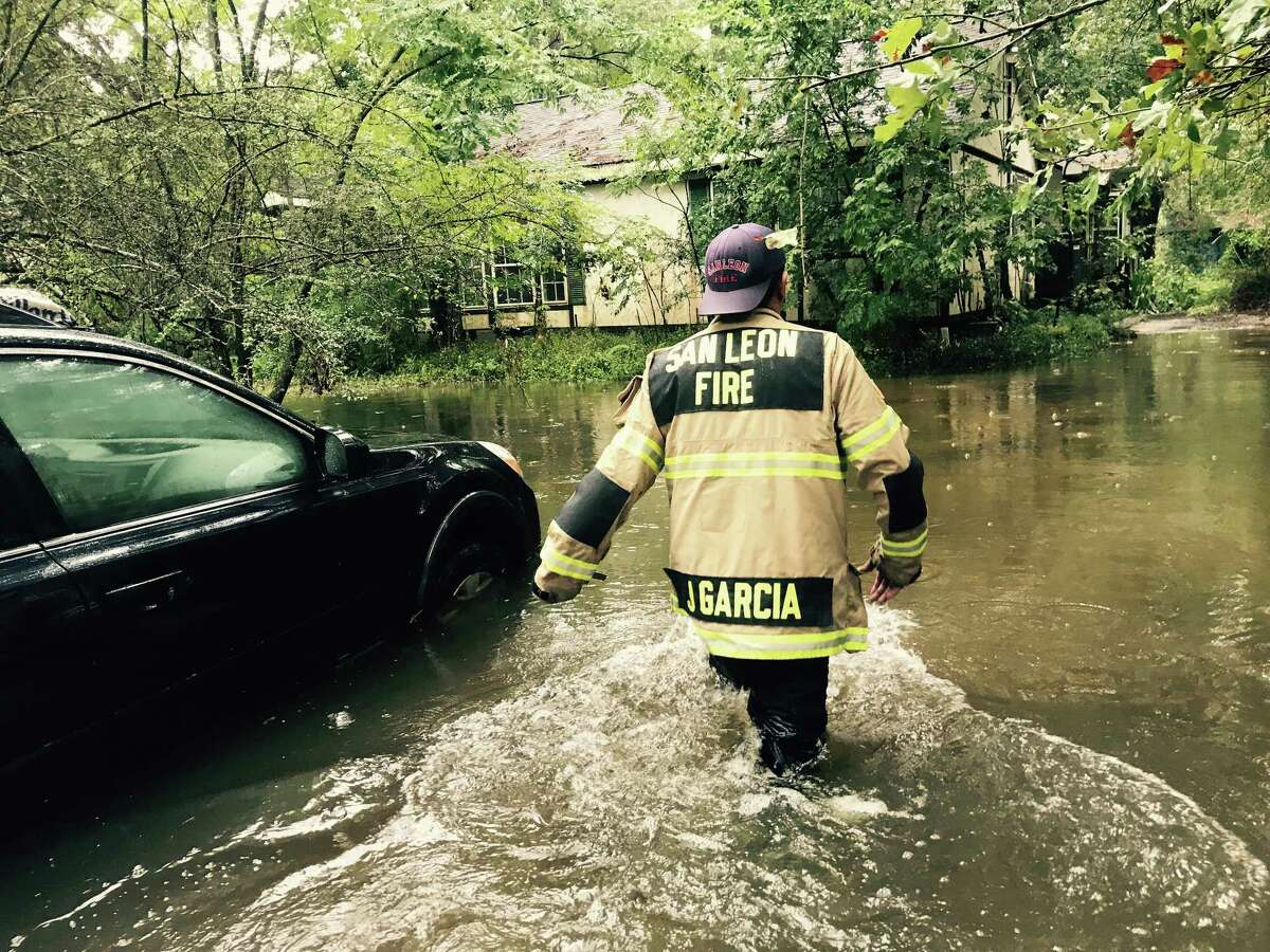 """Volunteer firefighter Jody Garcia goes house to house in a Dickinson neighborhood seeking residents who need help. """"Everyone is doing what they can,"""" Garcia said. """"It's awesome to see."""""""